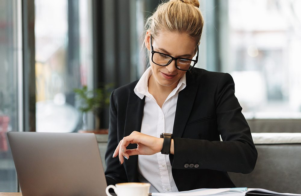 Cheerful business woman looking at watch.